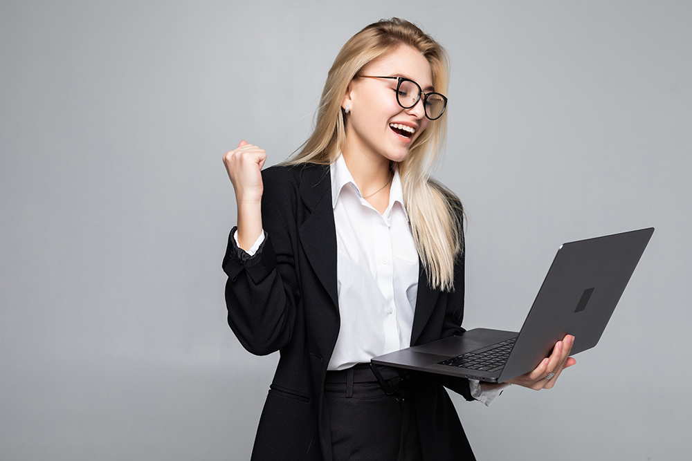 Portrait Of A Young Happy Business Woman With A Laptop With Win Gesture Over Gray Background